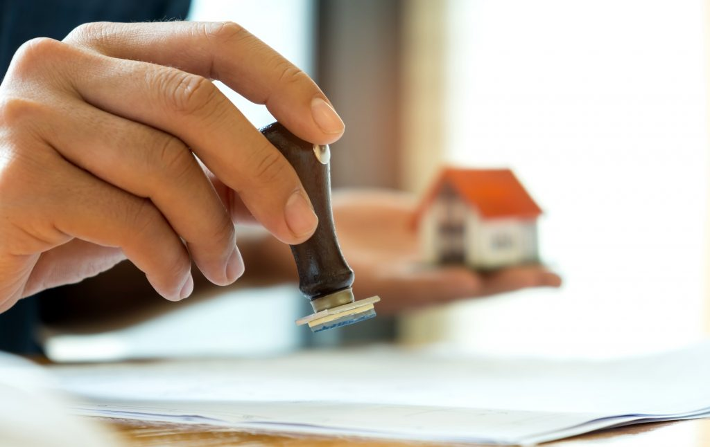 Close-up rubber stamp and model house in hand.